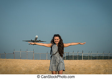 Jet plane takes off on the background behind a young woman
