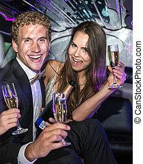Jet set couple drinking champagne
