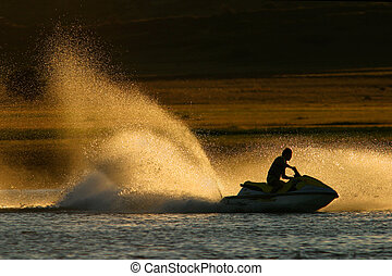 Backlit jet ski water spray, late afternoon