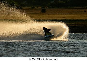 Jet ski action - Backlit jet ski with water spray, late...