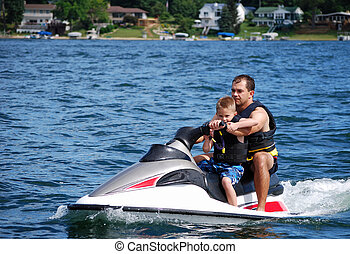 a young boy and his dad take a ride on a personal water craft