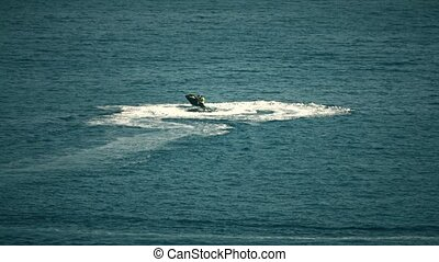 Jet ski riders having fun at sea. Telephoto lens shot - Jet...