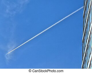 jet trail and offices building on blue sky