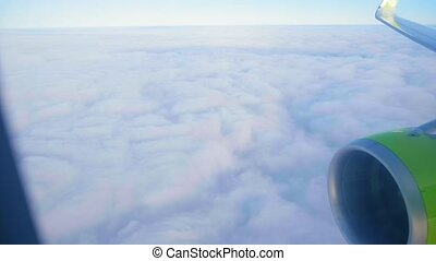 jetliner flies above white dense clouds under blue sky in evening with close green turbine and wing seen outside window