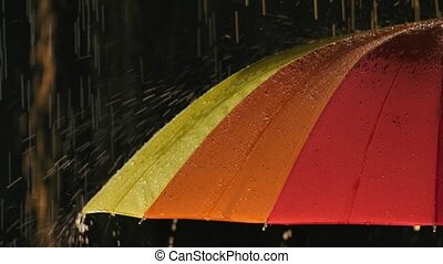 Jets of rain flow down the open rainbow umbrella. Umbrella without anyone on a black studio background. Close up. Slow motion.