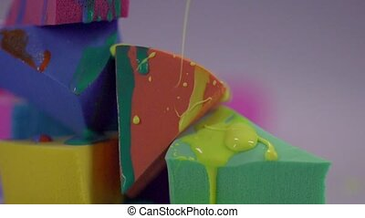 Jets of yellow nail polish fall on sponge.