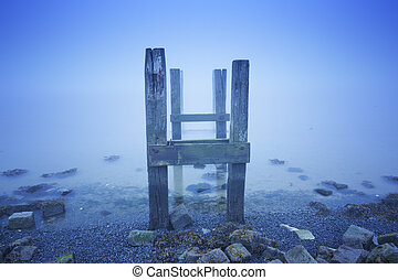 Jetty in the sea on a foggy morning at dawn