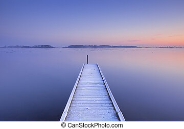 Jetty on a still lake in winter in The Netherlands