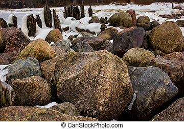 Jetty Pillars and Rocks Covered witn Snow in a Cloudy Winter Day