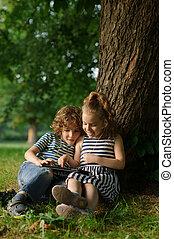 jeu, grand, asseoir, tablet., parc, deux, arbre, sous, enfants