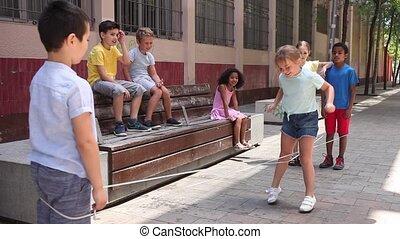 jeu, rue, bande, heureux, amis fille, sauter, peu, caoutchouc