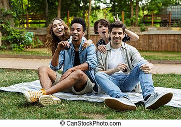 jeune, amis, dehors, dans parc, amusant, poser, boire, soda.