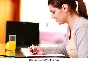 jeune, beau, femme heureuse, écriture note, chez soi