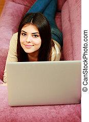jeune, belle femme, mensonge, sofa, à, ordinateur portable, chez soi