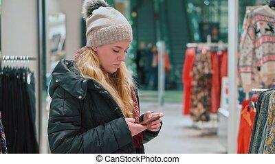 jeune, centre commercial, regarde, elle est, girl, magasin, habillement, smartphone., séduisant