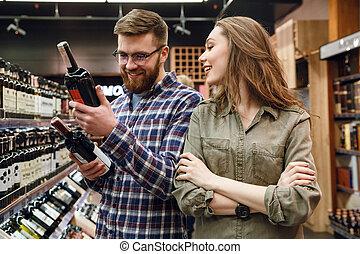 jeune couple, choisir bouteille, de, vin