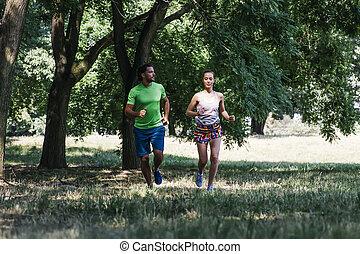 jeune couple, courant, dans parc, sur, a, jour ensoleillé