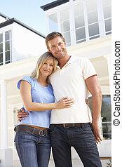 jeune couple, debout, dehors, maison rêveuse