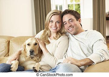 jeune, couple heureux, à, chien, s'asseoir sofa