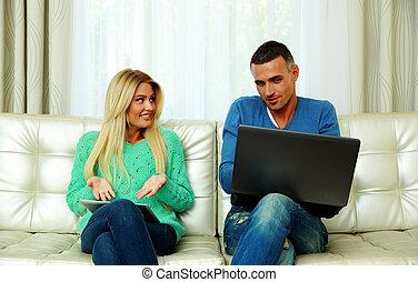 jeune couple, séance divan, et, utilisation, tablette, informatique, à, ordinateur portable, chez soi