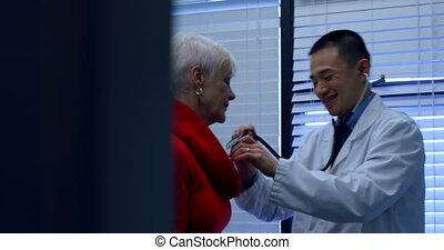 jeune docteur, asiatique, vue, patient, côté, mâle, clinique, 4k, examiner, personne agee