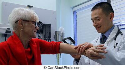 jeune docteur, asiatique, vue, patient, loupe, côté, mâle, clinique, examiner, personne agee