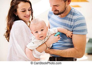jeune famille, à, a, dorlotez garçon, chez soi, debout, et, poser, pour, les, photo.