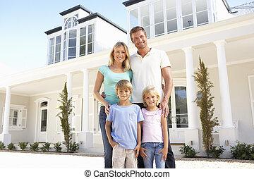 jeune famille, debout, dehors, maison rêveuse
