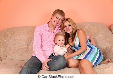 jeune famille, sur, sofa, dans, salle rose, 2