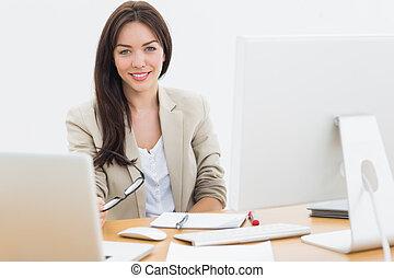 jeune femme, à, ordinateurs, bureau, dans, bureau