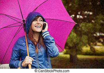 jeune femme, à, téléphone portable, sur, jour pluvieux