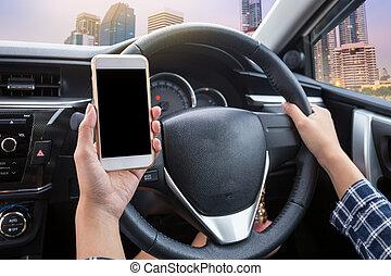 jeune femme, chauffeur, utilisation, écran tactile, smartphone, et, possession main, volant, dans voiture, à, ville, à, crépuscule, temps, fond