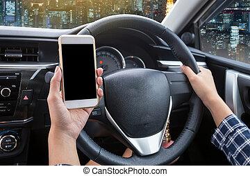 jeune femme, chauffeur, utilisation, écran tactile, smartphone, et, possession main, volant, dans voiture, à, nuit, ville, fond
