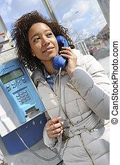 Jeune femme dans une cabine téléphonique