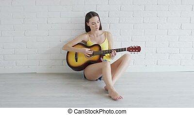 jeune femme, guitare, appareil photo, regarder