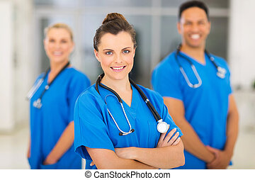 jeune, femme, infirmière, à, collègues, arriere-plan