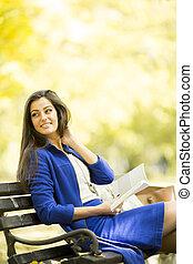 jeune femme, lecture livre, dans parc