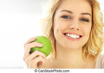 jeune femme, manger pomme, chez soi