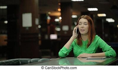 jeune femme, parler téléphone, a, tablette, informatique, coucher côté, a, table