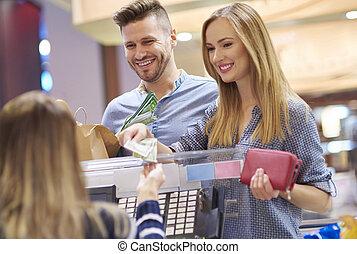 jeune femme, payant, par, espèces, dans, magasin