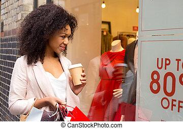 jeune femme, regarder dans, a, magasin, veuve, à, a, café, et, achats, bags.