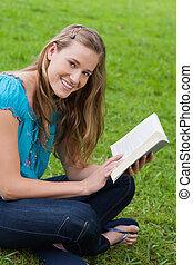jeune, femme souriante, regarder appareil-photo, quoique, lecture livre