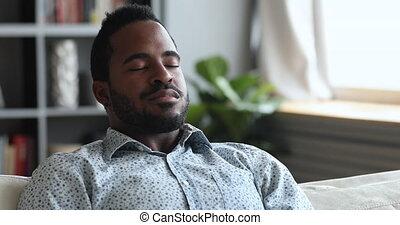 jeune, fermé, sofa, homme, méditer, africaine, yeux, calme