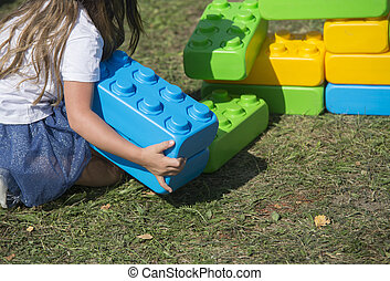 jeune fille, jouer, briques, dans jardin