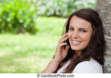 jeune, heureux, girl, séance, dans, a, parc, quoique, utilisation, elle, cellphone, et, regarder appareil-photo