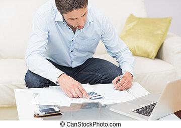 jeune homme, à, factures, calculatrice, et, ordinateur portable, chez soi