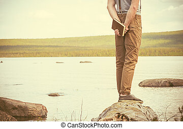 jeune homme, à, livre, debout, extérieur, à, lac, arriere-plan, été, vacances, et, style de vie, concept, retro, couleurs