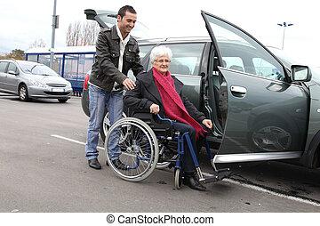 jeune homme, aider, femme aînée, dans, fauteuil roulant