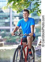 jeune homme, cyclisme, côté, rivière, dans, reglage urbain