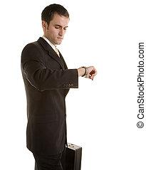 jeune homme, dans, complet, à, serviette, regarder montre